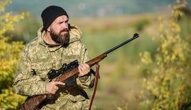 Cacciatore barbuto spendere caccia di svago Fuoco e concentrazione di cacciatore con esperienza Regolamento di caccia caccia fotografia stock
