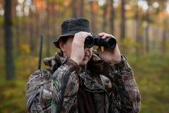 Cacciatore che esamina il binocolo Fotografia Stock