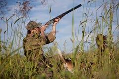 Cacciatore che mira la caccia, cani che aspettano il colpo Immagini Stock
