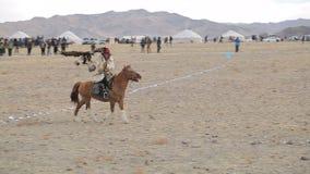 Cacciatore che monta un cavallo con l'aquila reale stock footage