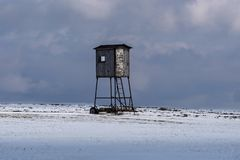 Cacciatore che posa sulle montagne russe in un campo nevoso Fotografie Stock Libere da Diritti