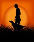 Cacciatore con il cane nel tramonto Fotografie Stock Libere da Diritti