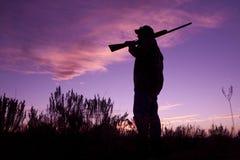 Cacciatore con il fucile da caccia nel tramonto immagine stock libera da diritti