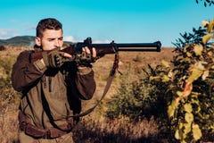 Cacciatore con il fucile potente con gli animali di macchia di portata Cacciatore con la pistola del fucile da caccia sulla cacci immagini stock libere da diritti