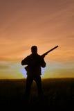 Cacciatore con il tramonto del fucile da caccia Fotografie Stock