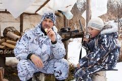 Cacciatore con suo figlio durante il resto sotto la tenda di caccia Immagini Stock