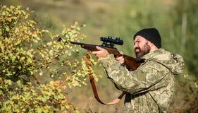 Cacciatore dell'uomo con la pistola del fucile Boot Camp Abilità di caccia ed attrezzature dell'arma Come caccia di giro nell'hob fotografia stock libera da diritti