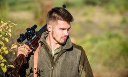 Cacciatore dell'uomo con la pistola del fucile Boot Camp Abilità di caccia ed attrezzature dell'arma Come caccia di giro nell'hob fotografia stock