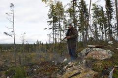 Cacciatore delle alci con un poco fuoco facendo uso del suo smartphone Fotografie Stock Libere da Diritti