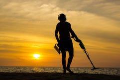 Cacciatore di tesoro con il metal detector sul tramonto la spiaggia Fotografia Stock Libera da Diritti