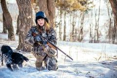Cacciatore femminile in vestiti del cammuffamento pronti a cercare, tenendo pistola a immagini stock