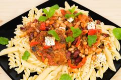 Cacciatore served on a black plate. Chichken thigh, bean, feta cheese and mint served on pasta Stock Photo