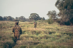Cacciatori che attraversano attraverso l'erba alta nel campo rurale durante la stagione di caccia Immagine Stock