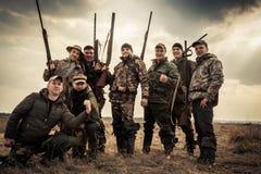Cacciatori che stanno insieme contro il cielo di alba nel campo rurale durante la stagione di caccia Concetto per lavoro di squad Immagini Stock Libere da Diritti