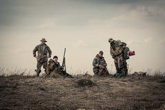 Cacciatori che stanno insieme contro il cielo di tramonto nel campo rurale durante la stagione di caccia immagini stock libere da diritti