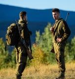 Cacciatori dell'uomo con la pistola del fucile Boot Camp Amicizia dei cacciatori degli uomini Forze dell'esercito camuffamento Mo fotografia stock libera da diritti