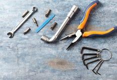 Cacciavite, chiavi di sfortuna, chiave a bussola e pezzi per un cacciavite su fondo di legno rustico immagini stock