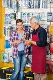 Cacciavite d'acquisto di Assisting Customer In del rappresentante Fotografia Stock Libera da Diritti
