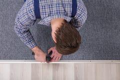 Cacciavite della radio di Installing Carpet With dell'installatore del tappeto immagine stock
