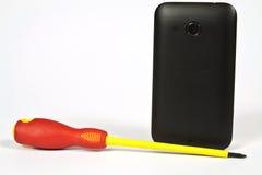 Cacciavite e un telefono cellulare Immagini Stock Libere da Diritti