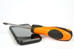 Cacciavite e un telefono cellulare Fotografia Stock Libera da Diritti