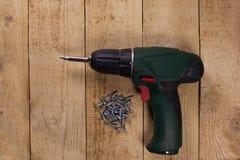 Cacciavite senza cordone sul pavimento di legno fotografia stock