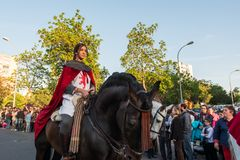A young rider on her horse in medieval dress during the celebration of Saint George and the dragon. stock photo