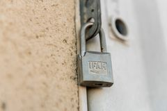 A broken IFAM lock closes the door of an electrical panel in Caceres, Extremadura, Spain. stock photo