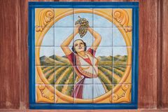 Painting of woman picking grapes in a vineyard drawn on tiles. royalty free stock images