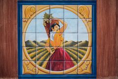 Painting of woman picking grapes in a vineyard drawn on tiles. royalty free stock photo