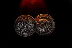 Metal medals inspired by the Stark house shields and Targaryen from the TV series Game of Thrones for sale as amulets. Caceres, Extremadura, Spain - March 13 stock photo