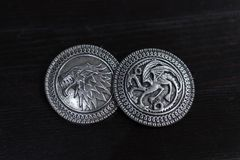 Metal medals inspired by the Stark house shields and Targaryen from the TV series Game of Thrones for sale as amulets. Caceres, Extremadura, Spain - March 13 stock images