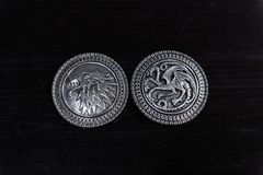Metal medals inspired by the Stark house shields and Targaryen from the TV series Game of Thrones for sale as amulets. Caceres, Extremadura, Spain - March 13 royalty free stock image