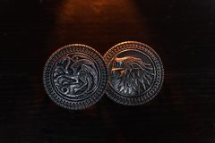 Metal medals inspired by the Stark house shields and Targaryen from the TV series Game of Thrones for sale as amulets. royalty free stock photo