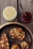 Cacerola con las crepes, atasco, miel rústica Foto de archivo libre de regalías