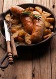 Cacerola con las patatas fritas y salchichas asadas a la parrilla, romero verde, bifurcación y cuchillo fotografía de archivo