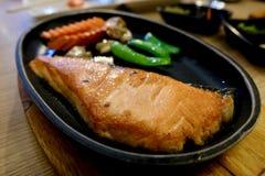 Cacerola de color salmón de Teriyaki frita en el de madera fotos de archivo
