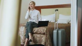 Cacerola de la empresaria sonriente en la camisa blanca usando en el ordenador portátil y hablando en el teléfono móvil mientras  metrajes
