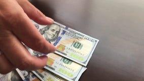 Cacerola de la mujer que cuenta hacia fuera centenares de dólares en efectivo almacen de metraje de vídeo