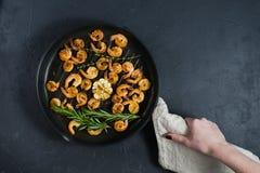 Cacerola de la tenencia del cocinero con los camarones fritos imagenes de archivo
