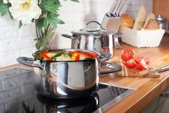 Cacerola en la estufa con las verduras en interior de la cocina Imágenes de archivo libres de regalías