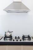 Cacerola inoxidable en estufa de gas con la capilla Fotografía de archivo