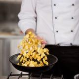 Cacerola masculina de Tossing Potatoes In del cocinero imagen de archivo