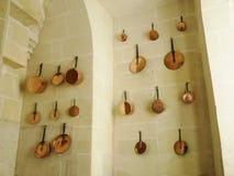 Cacerolas de cobre en la pared de una cocina medieval Imagen de archivo libre de regalías