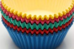 Cacerolas de papel coloreadas que cuecen las tazas para las magdalenas y los molletes Imagen de archivo libre de regalías