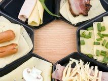 Cacerolas de Raclette con el alimento, ideal para el partido Fotografía de archivo libre de regalías