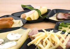 Cacerolas de Raclette con el alimento, ideal para el partido Fotos de archivo