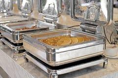 Cacerolas de vapor de la alimentación en la tabla de comida fría Fotografía de archivo libre de regalías