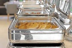 Cacerolas de vapor de la alimentación en la tabla de comida fría Imagen de archivo