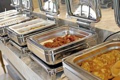 Cacerolas de vapor de la alimentación en la tabla de comida fría Foto de archivo libre de regalías